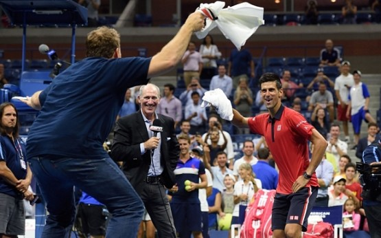 Novak Djokovic of Serbia (R) dances on the court with a fan after defeating Andreas Haider-Maurer of Austria during their US Open 2015 second round men's singles match at the USTA Billie Jean King National Center September 2, 2015  in New York. AFP PHOTO/DON EMMERTDON EMMERT/AFP/Getty Images